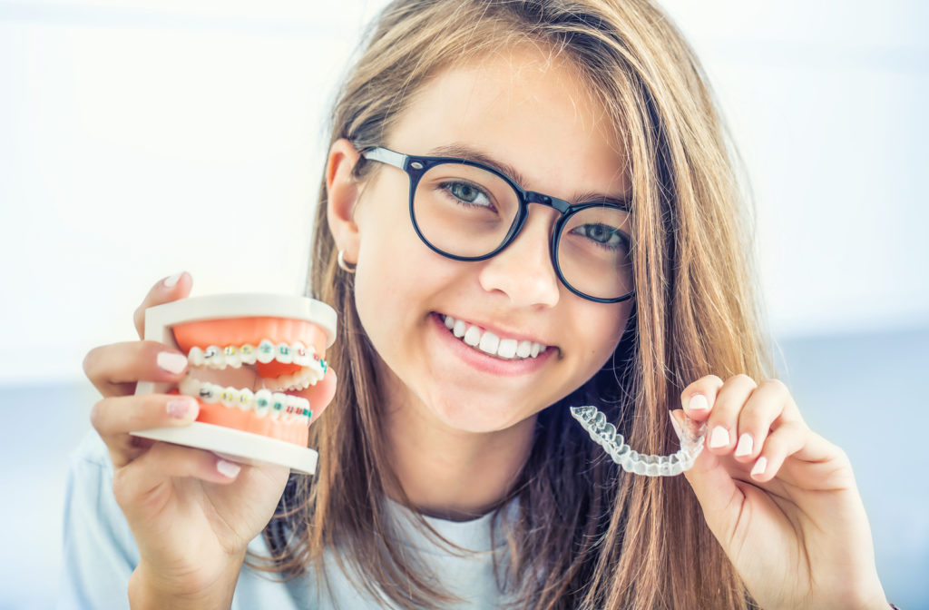 Dental invisible braces or silicone trainer in the hands of a young smiling girl