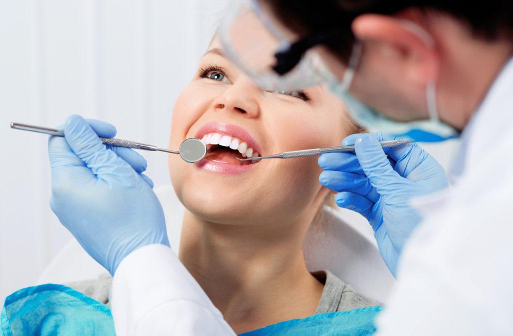 Dentist preparing happy patient for dental filling