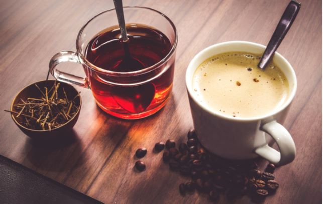 Cup of tea and coffee placed on wooden table